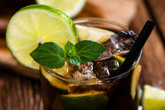 Cold Longdrink (Cuba Libre). With brown rum and fresh lime on rustic wooden background stock photos