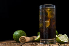Cold Longdrink (Cuba Libre). With brown rum and fresh lime on rustic wooden background royalty free stock photo