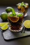 Cold longdrink on dark background. Cuba Libre or long island iced tea cocktail with strong drinks, cola, lime and ice in glasss, cold longdrink on dark royalty free stock images