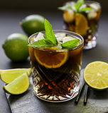 Cold longdrink on dark background. Cuba Libre or long island iced tea cocktail with strong drinks, cola, lime and ice in glasss, cold longdrink on dark stock images