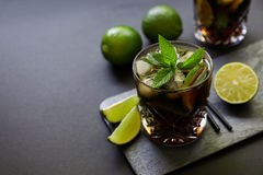 Cold longdrink on dark background. Cuba Libre or long island iced tea cocktail with strong drinks, cola, lime and ice in glasss, cold longdrink on dark stock photography
