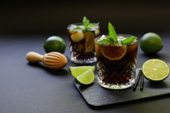Cold longdrink on dark background. Cuba Libre or long island iced tea cocktail with strong drinks, cola, lime and ice in glasss, cold longdrink on dark royalty free stock photos