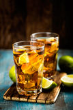 Cold longdrink or lemonade. Cuba Libre or long island iced tea cocktail with strong drinks, cola, lime and ice in glass, cold longdrink royalty free stock photography