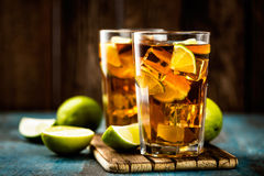 Cold longdrink or lemonade. Cuba Libre or long island iced tea cocktail with strong drinks, cola, lime and ice in glass, cold longdrink royalty free stock image
