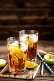 Cold longdrink or lemonade. Cuba Libre or long island iced tea cocktail with strong drinks, cola, lime and ice in glass, cold longdrink stock photo