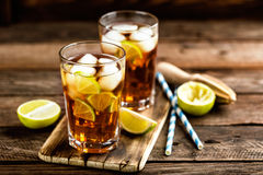 Cold longdrink or lemonade. Cuba Libre or long island iced tea cocktail with strong drinks, cola, lime and ice in glass, cold longdrink stock images