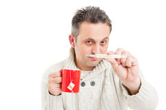Cold man holding mug and showing thermometer Stock Image
