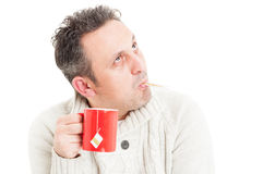Cold man holding mug and  thermometer in mouth Stock Image