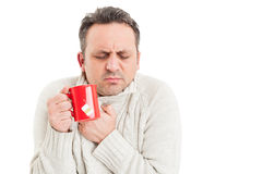 Cold man holding tea mug and shivering or freezing Stock Images