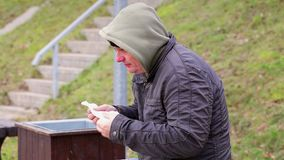 Cold man with napkin near nose at outdoors on the bench stock video footage
