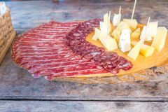 Cold meat plate on cutting board on wooden background Royalty Free Stock Images
