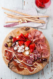Cold meat plate and grissini. Bread sticks on wooden background royalty free stock photos