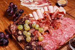 Cold meat plate. Slices prosciutto, ham,beef jerky,sausage, salami with grapes and spice on wooden cutting board Stock Photo
