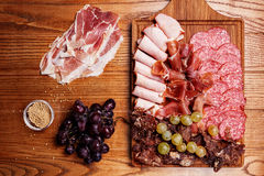 Cold meat plate. Slices prosciutto, ham,beef jerky,sausage, salami with grapes and spice on wooden cutting board Royalty Free Stock Images