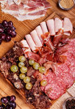 Cold meat plate. Slices prosciutto, ham,beef jerky,sausage, salami with grapes and spice on wooden cutting board Stock Photos