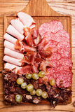 Cold meat plate on wooden cutting board. Cold meat plate, slices prosciutto, ham,beef jerky,sausage, salami with grapes and spice on wooden cutting board Royalty Free Stock Images