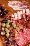Cold meat plate on wooden cutting board. Cold meat plate, slices prosciutto, ham,beef jerky,sausage, salami with grapes and spice on wooden cutting board Stock Photos