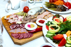 Cold meats on wooden plate on banquet table Stock Images