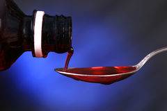 Cold medicine. Red cold medicine being poured into a spoon with blue background Royalty Free Stock Photography