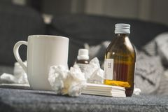 Cold medicine, cough syrup, hot beverage, paper towels and tissues to beat sickness, fever or flu. stock photography