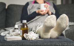 Cold medicine and sick woman drinking hot beverage to get well f. Rom flu, fever and virus. Dirty paper towels and tissues on table. Ill person wearing warm Stock Photo