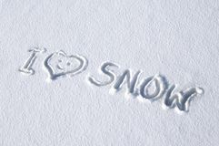 Cold Message but a warm sentiment. I love snow is handwritten in a blanket of snow.  A smiley heart replaces the word love in message Stock Photography