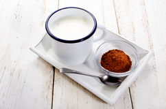 Cold milk in a enamel cup and cocoa in a glass bowl Royalty Free Stock Photography