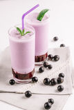 Cold milkshake with a black currant on a white background, close-up. Cold milkshake with a black currant on a white background Royalty Free Stock Photo