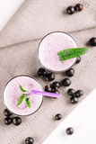 Cold milkshake with a black currant on a white background, close-up. Cold milkshake with a black currant on a white background Stock Photography