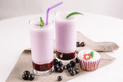 Cold milkshake with a black currant on a white background, close-up. Cold milkshake with a black currant on a white background Royalty Free Stock Images