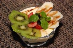Milky desert with kiwi, cherry, banana, mint and chocolate toping stock photography