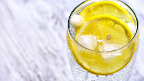 Cold mineral water with ice and lemon. Royalty Free Stock Photos