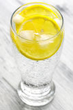 Cold mineral water with ice and lemon. Stock Photos