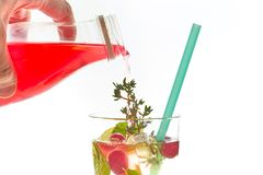Man pours cold berry cocktail in glass with ice, isolated on white background. summer refreshing drink with straw. Free space for stock image