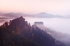 Cold misty daybreak in a fall valley of Bohemian Switzerland park. Hill with hut on the peak increased from magical darkness. Stock Images