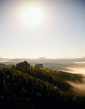 Cold misty daybreak in a fall valley of Bohemian Switzerland park. Hill with hut on the peak increased from magical darkness. Royalty Free Stock Images