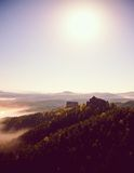 Cold misty daybreak in a fall valley of Bohemian Switzerland park. Hill with hut on the peak increased from magical darkness. Royalty Free Stock Photography