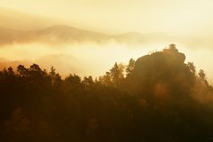 Cold misty daybreak in a fall valley of Bohemian Switzerland park. Hill with hut on the peak increased from magical darkness. Royalty Free Stock Photos
