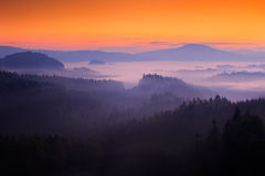 Cold misty foggy morning with twilight sunrise in a fall valley of Bohemian Switzerland park. Hills with fog, landscape of Czech R Royalty Free Stock Photos