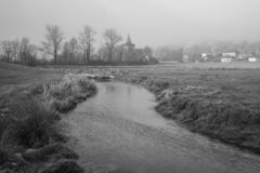 Cold misty Winter landscape over stream in English countryside b. Cold foggy Winter landscape over stream in English countryside black and white image Royalty Free Stock Images