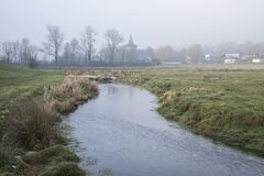 Cold misty Winter landscape over stream in English countryside. Cold foggy Winter landscape over stream in English countryside Royalty Free Stock Photo