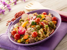 Cold mixed pasta salad with tuna. Tomatoes radish and peas Royalty Free Stock Photo