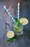Cold mojito cocktail with ice and straw on board Stock Photos