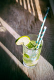 Cold mojito cocktail with ice and straw on board Royalty Free Stock Images