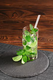 Cold mojito with ice and lime. Green mojito with rum or liquor on a wooden background. Refreshing alcoholic drinks. Copy space. stock images