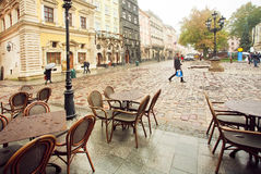 Cold morning on cobbled streets with empty outdoor restaurants of the Old Town. LVIV, UKRAINE - OCT 20: Cold morning on cobbled streets with empty outdoor Stock Photos