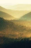 Cold morning at the end of summer. Colorful summer morning with strong golden rays and colorful fog between hills Stock Photo