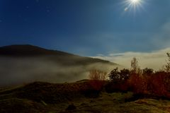 Cold morning fog on a hillside meadow near mountain at night in moon light. Cold morning fog on a hillside meadow near mountain village at night in moon light Stock Photography