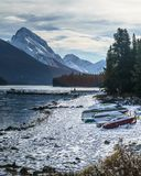 Cold morning with snow covering canoes in maligne lake, alberta, canada stock image