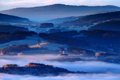 Cold morning in Sumava National park, hills and villages in the fog and rime, misty view on czech landscape, blue winter scene, Tr Royalty Free Stock Photos
